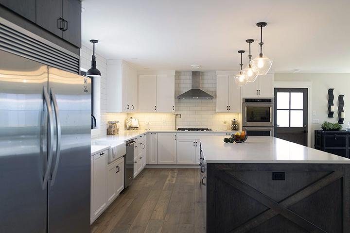 Modern Farmhouse Renovation in a kitchen with a large island, sub-zero refrigerator, farmer sink and elegant contemporary lighting. Design by MATERIA Interior Design Studio in British Columbia.