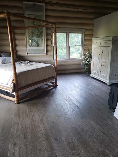 Log cabin home interior with Pekoe hardwood floors in a bedroom